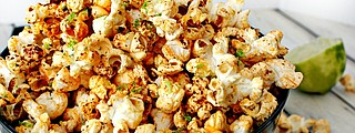Making savory popcorn at home helps cut the salt in fun snacks served to football game guests.