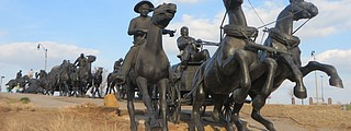 At OKC's Centennial Crossing, large scale sculptures depict the Oklahoma Land Run. Photo by Debbie Stone